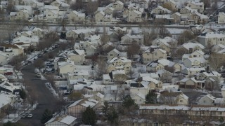 AX124_233 - 6K stock footage aerial video orbit Salt Lake City tract homes with snowy rooftops at sunrise, Utah