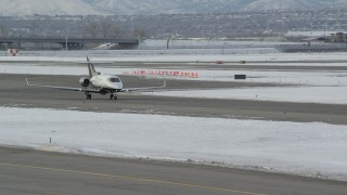AX124_235 - 6K stock footage aerial video of tracking civilian jet at SLC Airport in winter at sunrise, Utah