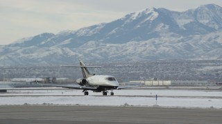 AX124_236 - 6K stock footage aerial video track civilian jet at Salt Lake City International Airport in winter at sunrise, Utah