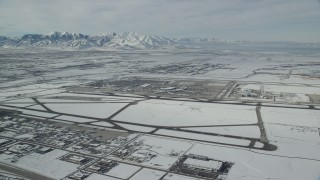 AX125_010 - 6K stock footage aerial video of Salt Lake City International Airport and jet on runway with winter snow in Utah