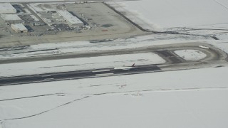AX125_011 - 6K stock footage aerial video track airliner landing at Salt Lake City International Airport with winter snow in Utah