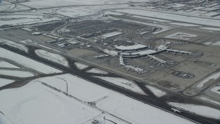 AX125_013 - 6K stock footage aerial video orbit terminals at SLC Airport with winter snow in Utah