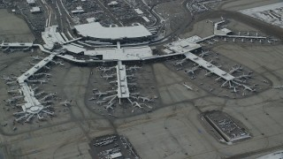 AX125_015 - 6K stock footage aerial video orbit Salt Lake City International Airport terminals with airliners and winter snow, Utah