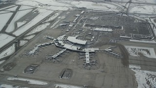 AX125_016 - 6K stock footage aerial video of orbiting SLC Airport terminals and parking lots with winter snow in Utah