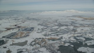 AX125_018 - 6K stock footage aerial video fly over frozen marshlands to approach snowy Antelope Island in winter, Utah