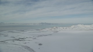 AX125_026 - 6K stock footage aerial video of Great Salt Lake and Antelope Island with snow mountains in winter in Utah