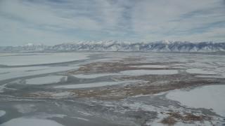 AX125_027 - 6K stock footage aerial video orbit snowy Wasatch Range mountains and frozen marshlands in winter, Utah