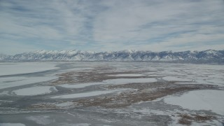 AX125_028 - 6K stock footage aerial video orbiting snowy Wasatch Range mountains seen from wintery marshlands in Utah
