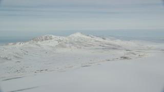 AX125_029 - 6K stock footage aerial video pan across snow mountains on Antelope Island in wintery Utah