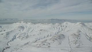AX125_034 - 6K stock footage aerial video flyby snowy Antelope Island mountains in wintertime, Utah