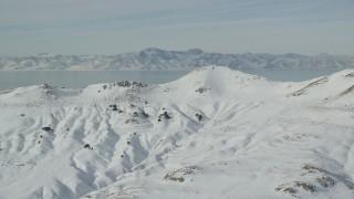 AX125_035 - 6K stock footage aerial video of snowy mountain summits on Antelope Island in winter, Utah