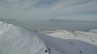 AX125_038 - 6K stock footage aerial video of the Great Salt Lake seen from snowy mountain summit on Antelope Island, Utah