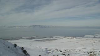 AX125_040 - 6K stock footage aerial video of Great Salt Lake seen from snowy ridge on Antelope Island in winter, Utah