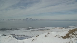 AX125_041 - 6K stock footage aerial video of Great Salt Lake and the frozen shore of Antelope Island in winter, Utah
