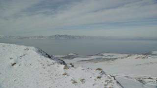 AX125_042 - 6K stock footage aerial video of snowy shore of Antelope Island and Great Salt Lake in wintertime, Utah