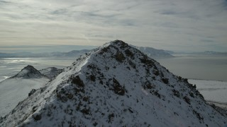 AX125_051 - 6K stock footage aerial video fly over snowy Antelope Island peak toward Great Salt Lake in winter, Utah