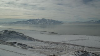 AX125_052 - 6K stock footage aerial video approach frozen shore of Antelope Island and Great Salt Lake in winter, Utah