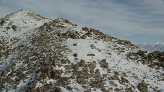 AX125_063 - 6K stock footage aerial video orbiting rocky slopes of a peak in winter with snow on Utah's Antelope Island
