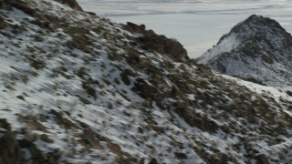 AX125_068 - 6K stock footage aerial video track a bighorn sheep racing across rocks and snow in wintertime, Antelope Island, Utah