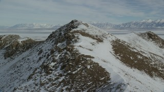 AX125_081 - 6K stock footage aerial video of flying over rocky ridge with winter snow on Antelope Island, Utah