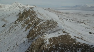 AX125_082 - 6K stock footage aerial video pan and fly over rocky mountain ridge with winter snow, Antelope Island, Utah