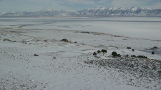 AX125_085 - 6K stock footage aerial video orbit sheets of ice on the Great Salt Lake seen from Antelope Island, Utah
