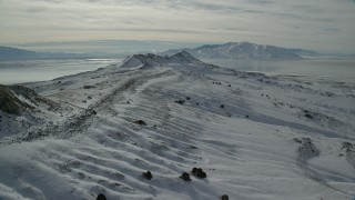 AX125_090 - 6K stock footage aerial video fly over snowy ground toward wintery mountains, Antelope Island, Utah