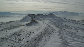 AX125_092 - 6K stock footage aerial video of approaching a snowy mountain ridge in winter on Antelope Island, Utah