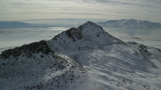 AX125_096 - 6K stock footage aerial video of approaching a mountain reak with winter snow on Antelope Island, Utah