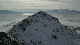 AX125_097 - 6K stock footage aerial video approach and fly over snowy peak near shore of Great Salt Lake, Antelope Island, Utah