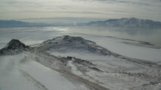 AX125_098 - 6K stock footage aerial video of a small snowy mountain near Great Salt Lake shore in winter, Antelope Island, Utah