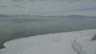 AX125_100 - 6K stock footage aerial video of Great Salt Lake with patches of ice seen from Antelope Island in winter, Utah