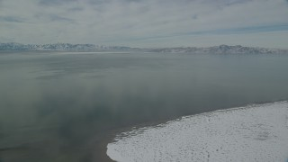 AX125_101 - 6K stock footage aerial video of Great Salt Lake with patches of ice and ringed by snow mountains, Utah
