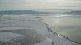 AX125_102 - 6K stock footage aerial video of a view of frozen marshland to Wasatch Range in winter, Utah