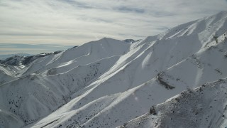 AX125_120 - 6K stock footage aerial video of winter snow on the Oquirrh Mountains of Utah