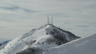 AX125_129 - 6K stock footage aerial video tilt to radio towers on the frozen summit of Farnsworth Peak, Utah