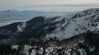 AX125_141 - 6K stock footage aerial video of snow mountains and trees in winter in Oquirrh Mountains, Utah