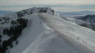 AX125_144 - 6K stock footage aerial video fly over snowy mountain slope to approach Nelson Peak in winter, Utah