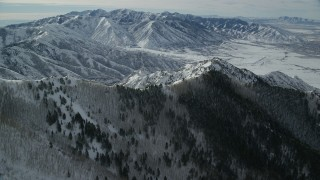 AX125_145 - 6K stock footage aerial video of snowy mountain ridges in Utah's Oquirrh Mountains in winter