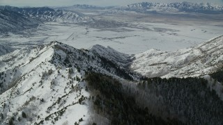 AX125_147 - 6K stock footage aerial video fly over Oquirrh Mountains to approach wintery small town in Utah