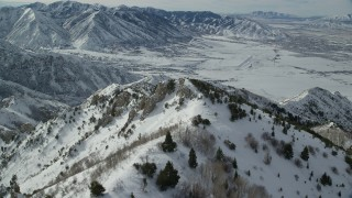 AX125_151 - 6K stock footage aerial video of flying over wintery Oquirrh Mountains to approach Tooele, Utah