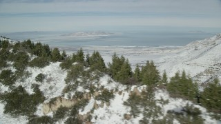 AX125_155 - 6K stock footage aerial video of Great Salt Lake seen from trees in the Oquirrh Mountains, Utah