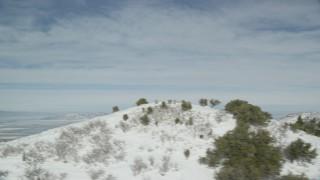 AX125_157 - 6K stock footage aerial video of Great Salt Lake seen from snowy mountain slope in wintertime, Utah