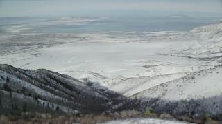 AX125_159 - 6K stock footage aerial video of Great Salt Lake seen from wintery mountains in Utah