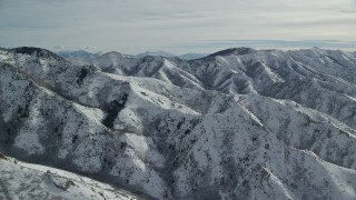 AX125_161 - 6K stock footage aerial video of rugged Oquirrh Mountains with snow in wintertime, Utah