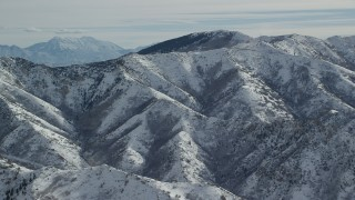 AX125_163 - 6K stock footage aerial video of Oquirrh Mountains slopes with light snow in wintertime Utah
