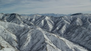 AX125_164 - 6K stock footage aerial video of light snow on Oquirrh Mountains in wintertime Utah
