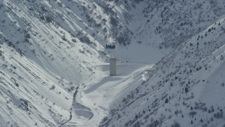 AX125_167 - 6K stock footage aerial video of Baltimore Gulch with lone building in the Oquirrh Mountains with snow, Utah