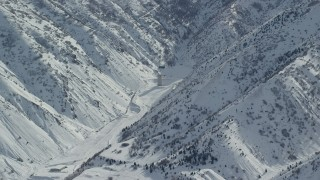 AX125_168 - 6K stock footage aerial video of a solitary building in Oquirrh Mountains' Baltimore Gulch with wintertime snow, Utah