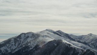AX125_179 - 6K stock footage aerial video of snowdrifts rising from Oquirrh Mountains peaks in winter, Utah
